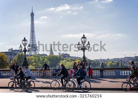 PARIS, FRANCE - SEPTEMBER 27: People on bicycles and pedestrians enjoying a car free day on Alexandre III bridge on September 27, 2015 in Paris, France - stock photo
