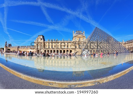 PARIS, FRANCE - SEPTEMBER 8, 2012: The entrance to Louvre -  glass pyramid fountain. Tourists resting on granite fence fountain. Traces in the sky jet - stock photo