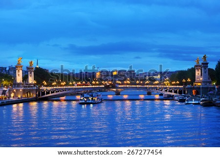 PARIS, FRANCE - SEPTEMBER 12, 2013: Trip boat on the Seine under the Pont Alexandre III. This bridge is widely considered as the most ornate in Paris - stock photo