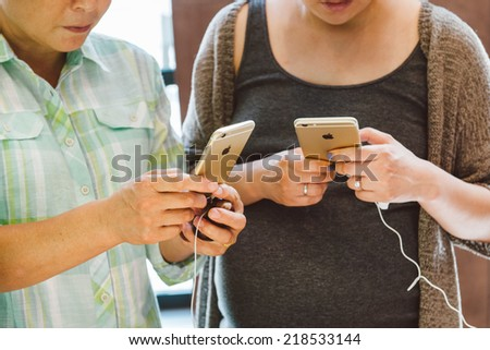PARIS, FRANCE - SEPTEMBER 20, 2014: Young couple looks at their new iPhone 6 and iphone 6 Plus during the sales launch at the Apple Inc. store in Paris, France - stock photo