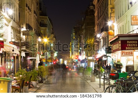PARIS, FRANCE - 19TH MARCH 2014: A view down a street in Paris at night showing the blurred motion of people and restaurants, cafes and other shops