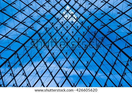 PARIS, FRANCE - 08.16.2004. - The Pyramid abstract metal and glass view inside the Louvre museum with blue sky - stock photo