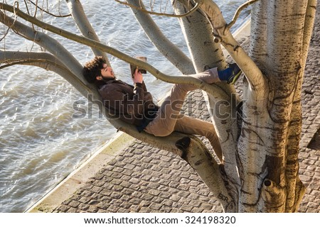 PARIS - Jan 2, 2014: A young man reading a book while reclining on a branch high up in a big tree on the bank of the Seine River, which is seen below. - stock photo
