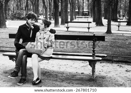 PARIS-JAN. 4, 2014: An unidentified couple sitting on a park bench at the Luxembourg Gardens, a popular romantic destination in Paris. Black and white image with grain added for a retro film effect. - stock photo