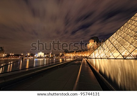 PARIS - JANUARY 8: Louvre Pyramid at dusk in Paris, France. Louvre is the biggest Museum in Paris displayed over 60,000 square meters of exhibition space. on January 8, 2012 in Paris, France - stock photo