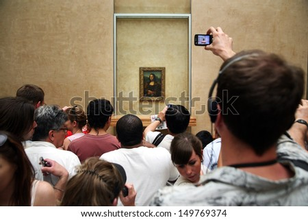 """PARIS - JULY 1: A crowd of visitors take photos of Leonardo DaVinci's """"Mona Lisa"""" at the Louvre Museum, July 1, 2009 in Paris, France. The painting is one of the world's most famous works of art. - stock photo"""