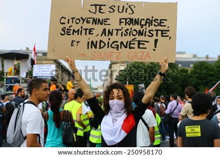 PARIS - JULY 23, 2014: A masked female protester holds up a sign at a pro-Palestine protest in Paris on July 23, 2014. Thousands demonstrated that summer to protest Israel's assault on the Gaza Strip. - stock photo