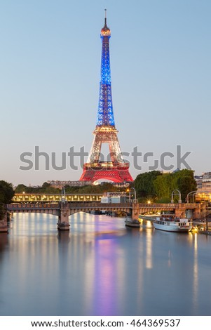 PARIS - JULY 18, 2016: Eiffel Tower at evening in colors of french flag with Seina river on foreground
