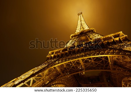 PARIS - JULY 10: Eiffel Tower by night, low angle view. The tower is the tallest structure in Paris and the most-visited paid monument in the world on July 10, 2014 in Paris.