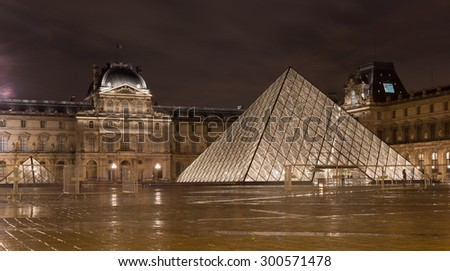 PARIS - July 19: Louvre museum in Paris, France at night on July 19, 2015. Louvre is the biggest museum in Paris with over 60,000 square meters of exhibition space. - stock photo