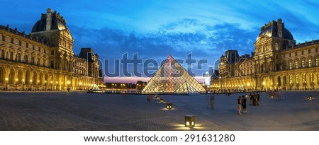 PARIS-JULY 31: Reflection of Louvre pyramid shines at dusk during the Summer Exhibition July 31, 2014 in Paris. - stock photo