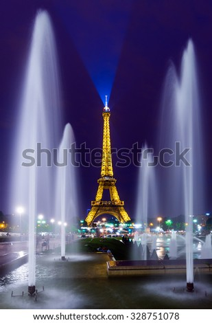 PARIS - JULY 19: The Eiffel Tower and Fountains of Warsaw seen at twilight on July 19, 2014 in Paris, France. The Fountains, built in 1937, were completely renovated in 2011.  - stock photo