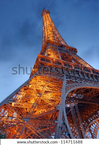 PARIS - JULY 26: The Eiffel Tower from below upwards in the evening on July 26, 2012 in Paris, France. The Eiffel Tower lit by more than 350 lamps mounted within the structure of the tower itself. - stock photo