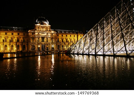 PARIS - JULY 1: The Louvre museum at night with its landmark main entryway the glass pyramid. The pyramid was designed by architect I. M. Pei and completed in 1989, Paris, France, July 1, 2009.