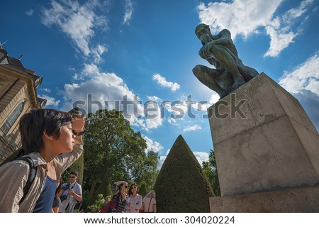 PARIS - JULY 25: tourists visiting the statue of the Thinker at the Museum of Rodin on July 25, 2015 in Paris,France.The Thinker is a world famous bronze sculpture made by Auguste Rodin in year 1880.  - stock photo
