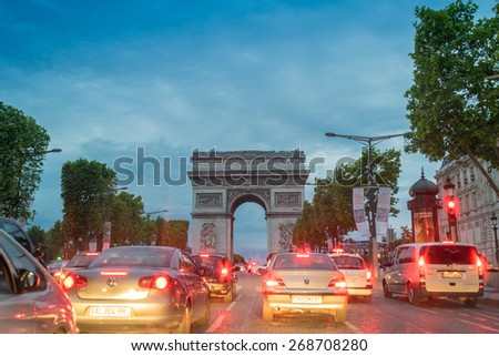 PARIS - JULY 7, 2014: Traffic along Triumph Arc at sunset. Traffic is a major issue for the french capital.