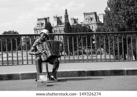 PARIS - JULY 6: Unidentified senior musician plays accordion on the bridge near  Hotel de Ville on July 6, 2013 in Paris, France. Dozens buskers perform on streets of Paris. - stock photo