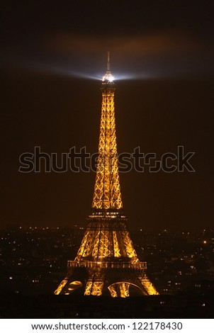 PARIS - JUNE 10: Illuminated Eiffel tower against black sky while the projector on top of it is illuminating the sky above on June 10, 2010 in Paris. Eiffel is the most visited monument in France.