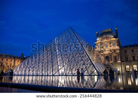 PARIS - JUNE 18: Long-exposure picture of the illuminated Pyramid that serves as one of the entrances to the Louvre Museum in Paris, with some tourists still walking around, on June 18, 2009. - stock photo