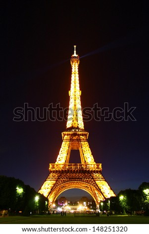 PARIS -JUNE 2, 2009: Romantic  park near the Eiffel Tower, June 2, 2009. Illuminated Eiffel Tower is particularly beautiful when seeing from the many parks in Paris, France. - stock photo