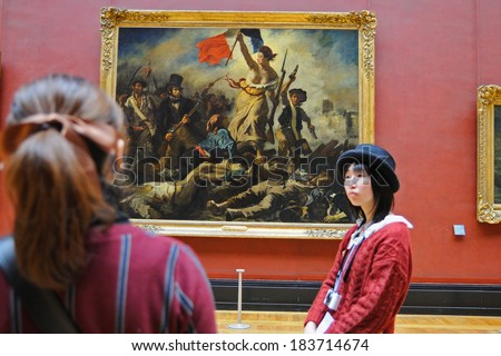 PARIS - MAR 1: Tourists look at the paintings of Eugene Delacroix at the Louvre Museum (Musee du Louvre) on March 1, 2014 in Paris, France. - stock photo