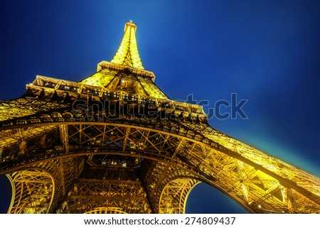 PARIS - MARCH 15 : Eiffel Tower brightly illuminated at dusk on MARCH 15, 2015 in Paris. The Eiffel tower is the most visited monument of France.