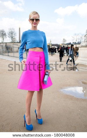 PARIS - MARCH 1, 2014: Stylish European woman with blue midriff and pink skirt in the Tuileries Garden. Paris Fashion Week: Ready to Wear 2014/2015 is held from February 25 to March 5, 2014. - stock photo