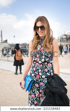 PARIS - MARCH 1, 2014: Stylish European woman with flower pattern one-piece dress in the Tuileries Garden. Paris is one of the capitals of fashion in the world.