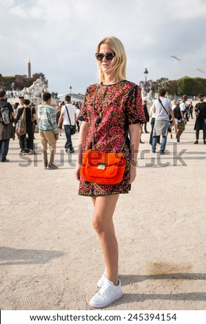 PARIS - MARCH 1, 2014: Stylish European woman with flower pattern one-piece dress in the Tuileries Garden. Paris is one of the capitals of fashion in the world. - stock photo