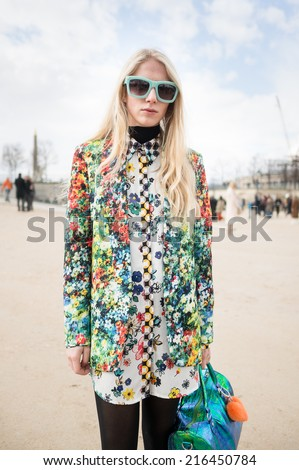 PARIS - MARCH 1, 2014: Stylish European woman with flower pattern vestment in the Tuileries Garden. Paris is one of the capitals of fashion in the world. - stock photo