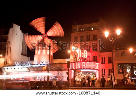 PARIS - MARCH 6: The Moulin Rouge at night, on March 6, 2012 in Paris, France. Moulin Rouge is a famous cabaret built in 1889 by Joseph Oller. People gather before show starts to get tickets. - stock photo