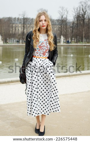 PARIS - MARS 5, 2013: Stylish European girl with black spots skirt in the Tuileries Garden. Paris Fashion Week: Ready to Wear 2013/2014 is held from February 26 to March 6, 2013. - stock photo