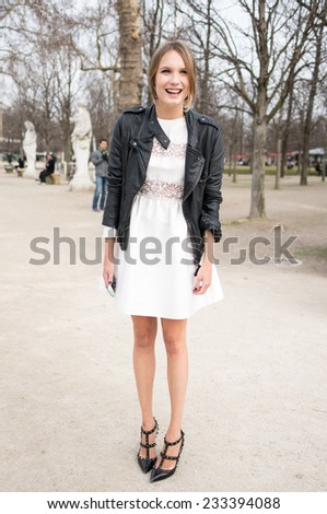 PARIS - MARS 5, 2013: Stylish European woman with white skirt and black leather jacket in the Tuileries Garden. Paris Fashion Week: Ready to Wear 2013/2014 is held from February 26 to March 6, 2013.