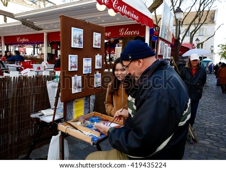 PARIS - May 3, 2016: A man painting in the streets of the French capital next to a chinese tourist