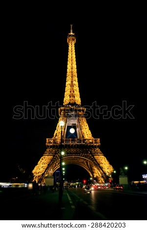 PARIS - MAY 27, 2015: Eiffel Tower brightly illuminated at dusk on May 27, 2015 in Paris. The Eiffel tower is the most visited monument of France.