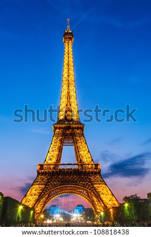 PARIS - MAY 22: Eiffel Tower brightly illuminated at dusk on May 22, 2008 in Paris. The Eiffel tower is the most visited monument of France. - stock photo