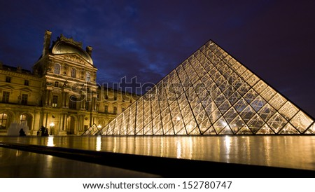 PARIS - NOV 21: Louvre pyramid shining at dusk during the Winter Exhibition on November 21,2012 in Paris.Louvre is the biggest Museum in Paris displayed over 60,000 square meters of exhibition space.