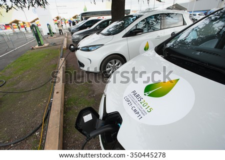PARIS - NOVEMBER 30: A fleet of electric cars charges in front fo the COP21 UN climate conference in Le Bourget near Paris, France, November 30, 2015. - stock photo
