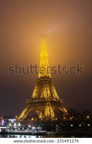 PARIS - NOVEMBER 30: Eiffel Tower and lights in evening fog  on November 30, 2014. The Eiffel tower is the most visited monument of France.