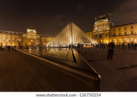 PARIS- NOVEMBER 30: The Louvre Art Museum on November 30, 2012 in Paris. The history of this most famous museum goes back 800 years of continuous transformations from fortress to palace and museum. - stock photo