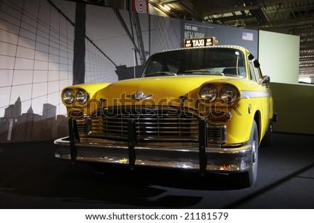PARIS - OCTOBER 13 : People look at a Yellow cab taxi of new york at the 2008 Paris Motor Show October 13, 2008 in Paris. - stock photo