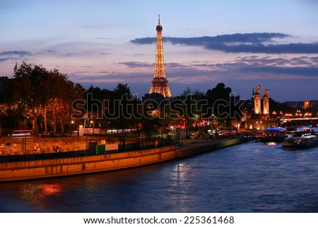 PARIS - OCTOBER 22: The illuminated Eiffel Tower in the evening on Oct. 22, 2014 in Paris, France.The Eiffel tower is most visited monument of France with 6 million visitors every year. - stock photo