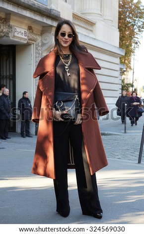 PARIS - OCTOBER 1: Woman poses for photographers before Chloe show with Chloe bag, Paris Fashion Week Day 3, Spring / Summer 2016 street style on October 1, 2015 in Paris. - stock photo