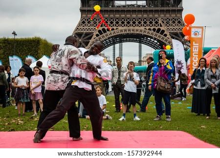 PARIS - SEPT 22: Two unidentified men demonstrate Jiu Jitsu on September 22, 2013 in Paris, France. Famillathlon, action for raising awareness to sport, takes place in Champ de Mars near Eiffel tower. - stock photo