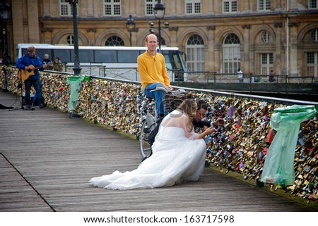 PARIS - SEPTEMBER 18: Bride and groom looking for their padlock, symbol of eternal love, in a bridge over the Seine river in Paris, France, on September 18, 2013. - stock photo