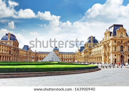 PARIS - SEPTEMBER 17. Glass pyramid and the Louvre museum on September, 17, 2013. The Louvre is the biggest museum in Paris with nearly 35,000 objects from prehistory to the 19th century . - stock photo