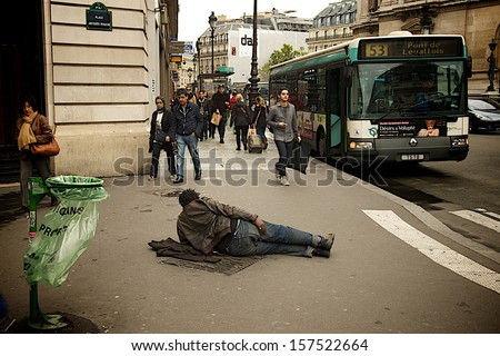 PARIS - SEPTEMBER 19: Homeless man laying on a busy street in Paris next to the Opera Garnier, reflecting Europe's social as well as financial situation, on September 19, 2013.  - stock photo