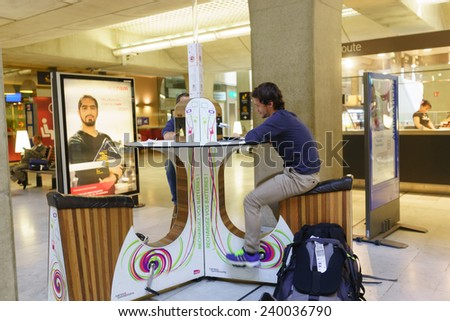 PARIS - SEPTEMBER 10: man charge phone in airport on September 10, 2014 in Paris, France. Paris Charles de Gaulle Airport, is one of the world's principal aviation centres - stock photo
