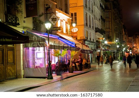 PARIS - SEPTEMBER 18: Romantic street cafe at night with several customers and pedestrians, many of them tourists in Paris, France, on September 18, 2013. - stock photo