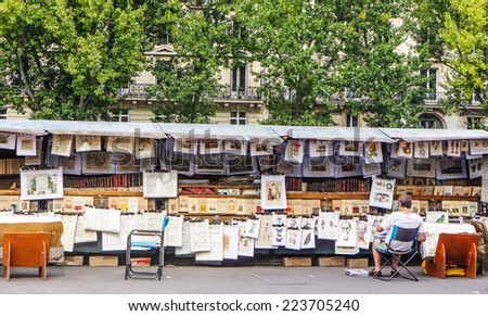 PARIS - SEPTEMBER 17: Second-hand book market on quay of river Seine near cathedral Notre Dame de Paris. It is based in 16 century. The event took palce on September 17, 2014 in Paris, France.  - stock photo